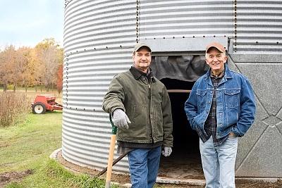 Two farmers standing in front of grain bin