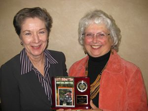Cheryl Tevis (left), 2008 recipient, presents plaque to Jan Goldsmith